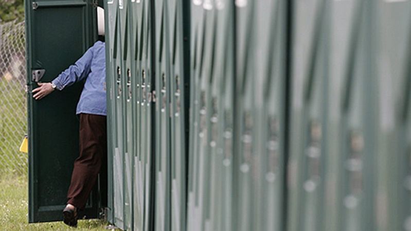 A woman utilizes the hundreds of porta-potties that are distributed throughout the 36th Winnipeg Folk Festival at Bird's Hill Park, which is just north east of Winnipeg, Friday July 10, 2009. (THE CANADIAN PRESS / John Woods)