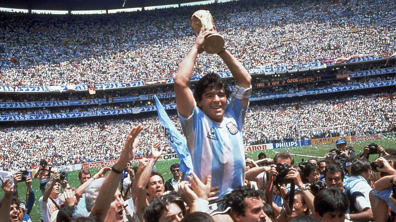 FILE - In this June 29, 1986, file photo, Diego Maradona, holds up the trophy, after Argentina beat West Germany 3-2 in the World Cup soccer final match, at the Atzeca Stadium, in Mexico City. The 21st World Cup begins on Thursday, June 14, 2018, when host Russia takes on Saudi Arabia. (AP Photo/Carlo Fumagalli, File)