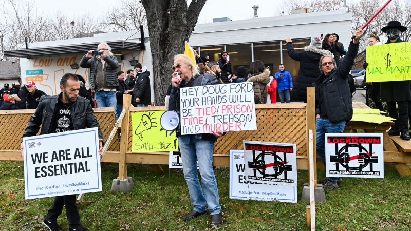 People protest at Adamson Barbecue as the restaurant and people defy provincial lockdown orders to shut down indoor and outdoor dining during the COVID-19 pandemic in Toronto on Wednesday, November 25, 2020. THE CANADIAN PRESS/Nathan Denette