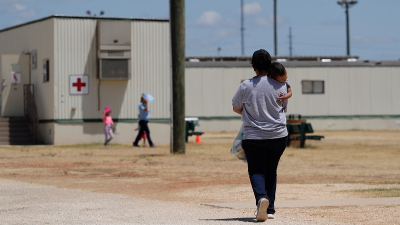 In this Aug. 23, 2019 file photo, immigrants seeking asylum walk at the ICE South Texas Family Residential Center, in Dilley, Texas. (AP Photo/Eric Gay, File)