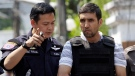 In this Feb. 20, 2012, file photo, an Iranian bomb suspect Mohammad Kharzei, right, listens to a Thai police officer as he is taken to verify the house where he and other Iranian compatriots rented in Bangkok, Thailand. (AP Photo/Sakchai Lalit, File)