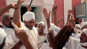 In this March 22, 1996 file photo, then opposition leader Sadiq Al-Mahdi, center left, is cheered by supporters as he walks out of the Wad Nubawi Mosque in Khartoum, Sudan. (AP Photo/Jean-Marc Bouju, File)