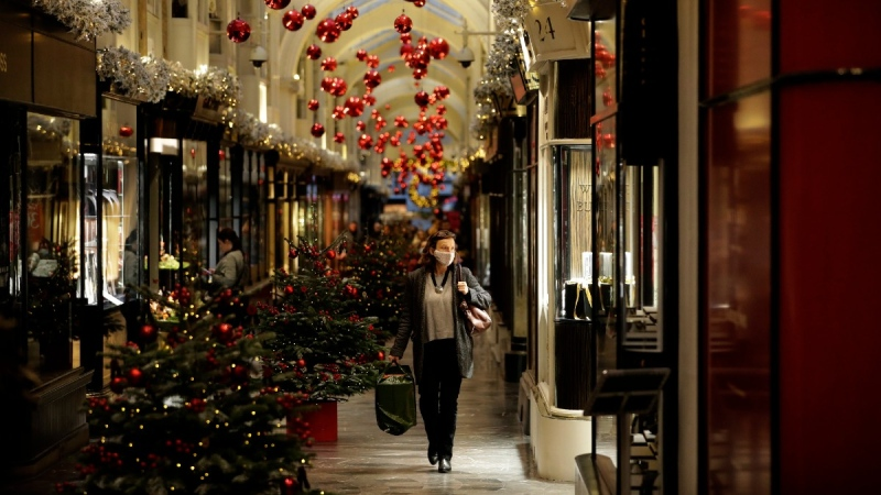 A woman wearing a face mask walks past Christmas trees and decorations in Burlington Arcade in London, on Nov. 25, 2020. (Matt Dunham / AP)
