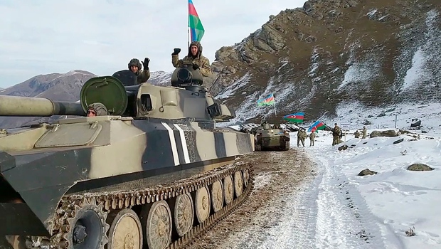 This photo taken from a video released by Azerbaijan's Defense Ministry on Wednesday, Nov. 25, 2020, shows Azerbaijan's army soldiers sitting atop of their military vehicle on a road in Kalbajar region of Azerbaijan. (Azerbaijan's Defense Ministry via AP)
