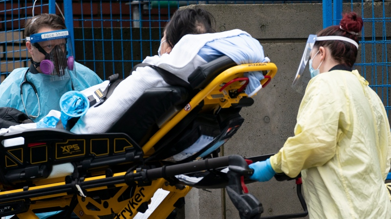 Medical personnel wear personal protective equipment to help prevent the spread of COVID-19 as they wheel a patient into St. Paul's hospital in downtown Vancouver Monday, November 23, 2020. THE CANADIAN PRESS/Jonathan Hayward