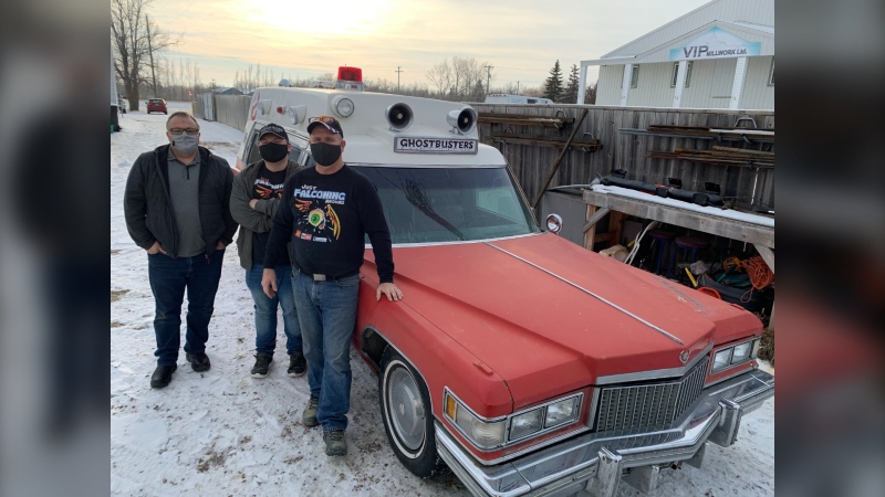 Paul Nairn (left), poses with Kelly and William Ducharme next to a Cadillac restored to look like the Ghostbusters vehicle. (CTV News Photo Jamie Dowsett)