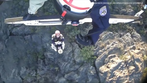 Caught on cam: Rescue crews come to the aide of a man who had been trapped under a boulder on a California mountainside for 12 hours.