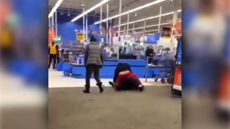 Video posted to social media shows a man punching another man on the floor of a Walmart store. (Facebook)