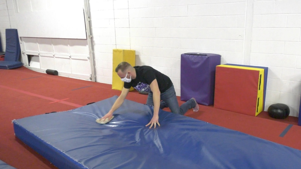 Eric Bestvater, the owner and head coach of Rebels Cheerleading Athletics, wipes down a mat at the team's facility. (Colton Wiens/CTV News)