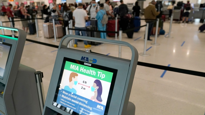 A kiosk displays a message encouraging wearing face masks and social distancing as passengers wait in line at Miami International Airport, Wednesday, Nov. 25, 2020, in Miami. (AP Photo/Lynne Sladky)