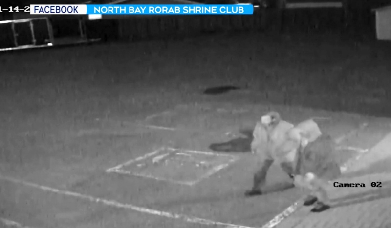 The club's security camera caught two people at around 1:30 a.m. on Nov. 14 carrying bolt cutters, approach the sheds and trailer and cut the locks. (Supplied)