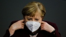 German Chancellor Angela Merkel adjusts her face mask as she arrives for a parliament session about German government's policies to combat the spread of the coronavirus and COVID-19 disease at the parliament Bundestag, in Berlin, Germany, Thursday, Nov. 26, 2020. (AP Photo/Markus Schreiber)