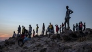 Tigray people who fled the conflict in Ethiopia's Tigray region, stand on a hill top over looking Umm Rakouba refugee camp in Qadarif, eastern Sudan, Thursday, Nov. 26, 2020. (AP Photo/Nariman El-Mofty)