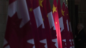 A Chinese flag is illuminated by sunshine in the Hall of Honour on Parliament Hill in Ottawa, Thursday September 22, 2016. (THE CANADIAN PRESS/Adrian Wyld)