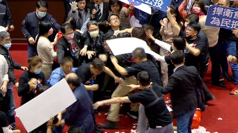 In this image made from video, lawmakers fight during a parliament session in Taipei, Taiwan, Friday, Nov. 27, 2020. (FTV via AP)