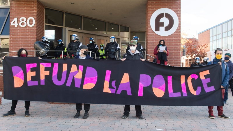 Protesters hold up a sign outside the Police Brotherhood during a defund the police demonstration in Montreal, Saturday, October 24, 2020, as the COVID-19 pandemic continues in Canada and around the world. THE CANADIAN PRESS/Graham Hughes