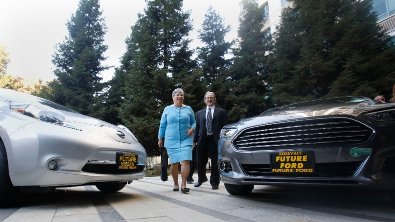 Mary Nichols, centre in blue, walks between a pair of zero-emission vehicles displayed in Sacramento, Calif., on Oct. 24, 2013. (Rich Pedroncelli / AP)
