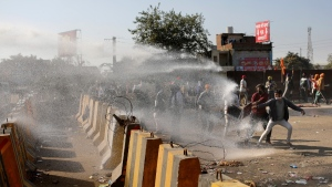 Police use water cannon to disperse protesting farmers at the border between Delhi and Haryana state, on Nov. 27, 2020. (Altaf Qadri / AP)