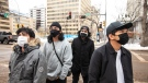 Pedestrians wears masks as they wait for the cross walk to change, as the COVID-19 numbers spike in Edmonton on Tuesday November 24, 2020. THE CANADIAN PRESS/Jason Franson