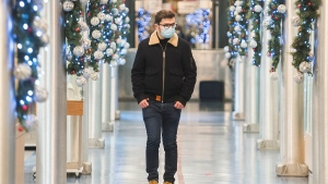 A man wears a face mask as he walks through an indoor market in Montreal, Sunday, November 22, 2020, as the COVID-19 pandemic continues in Canada and around the world. THE CANADIAN PRESS/Graham Hughes