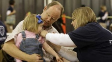 Dan Brundage holds his daughter, Caroline Brundage, as she receives the swine flu vaccine from nurse Diane Buergler in Indianapolis, Thursday, Oct. 22, 2009. (AP Photo/Darron Cummings)