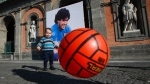 16-month-old Andrea Cangiano plays with a ball in front of an image of Diego Maradona at Naples' Royal Palace in the central Piazza Plebiscito, on Nov. 27, 2020. (Alessandra Tarantino / AP)