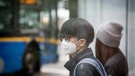 A man wears a mask over his mouth and nose while waiting for a bus in downtown Vancouver, on Thursday, Jan. 23, 2020. (Darryl Dyck / THE CANADIAN PRESS)