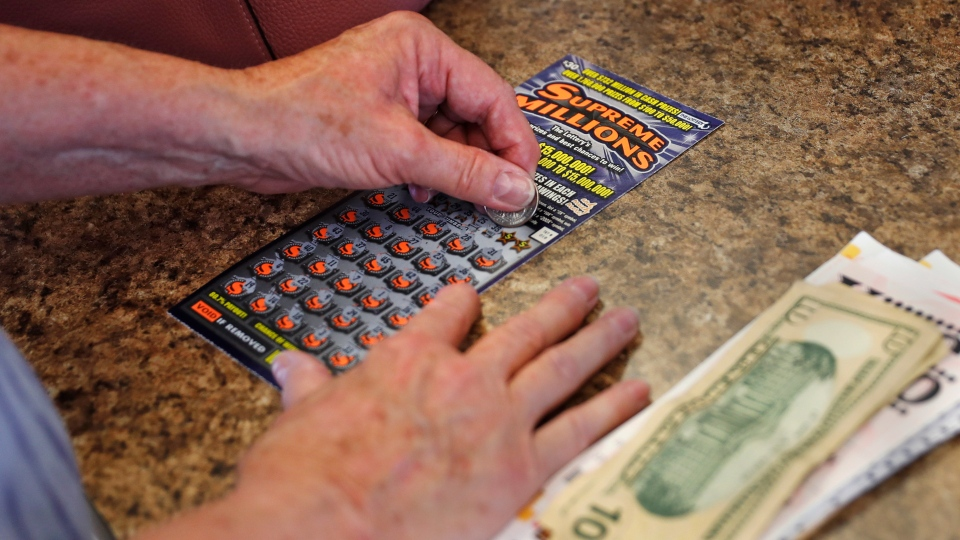 A woman scratches a $30 instant ticket while playing the lottery at Ted's Stateline Mobil on Wednesday, June 24, 2020 in Methuen, Mass. (AP Photo/Charles Krupa)