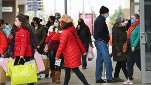 People line up at the Toronto Premium Outlets mall on Black Friday for shopping sales during the COVID-19 pandemic in Milton, Ont., Friday, Nov. 27, 2020. Halton and York region is still open for in person shopping as Toronto and Peel are in lockdown. THE CANADIAN PRESS/Nathan Denette