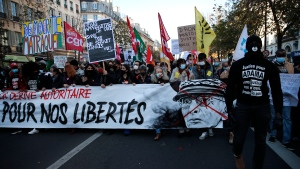 """Protester hold a banner reading """"For our freedom"""" and showing a defaced portrait of Paris police prefect Didier Lallement during a demonstration against a security law that would restrict sharing images of police, Saturday, Nov. 28, 2020 in Paris. (AP Photo/Francois Mori)"""