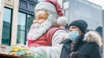 A shopper walks past a Christmas display on Montreal's Saint-Catherine Street in Montreal, Friday, Nov. 27, 2020. THE CANADIAN PRESS/Paul Chiasson