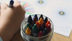 A child colours in a book using crayons (Pixabay Stock Photo).