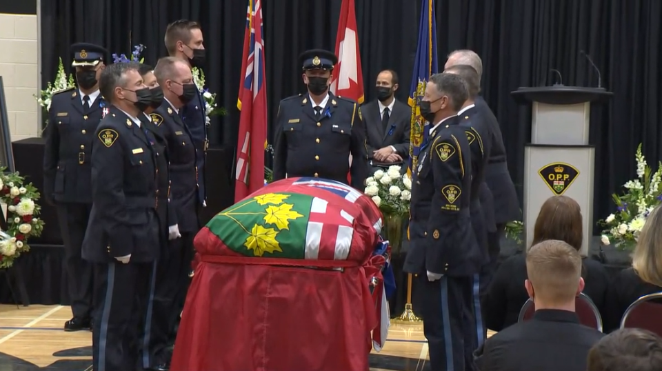 Pallbearers for Const. Marc Hovingh stand at caske