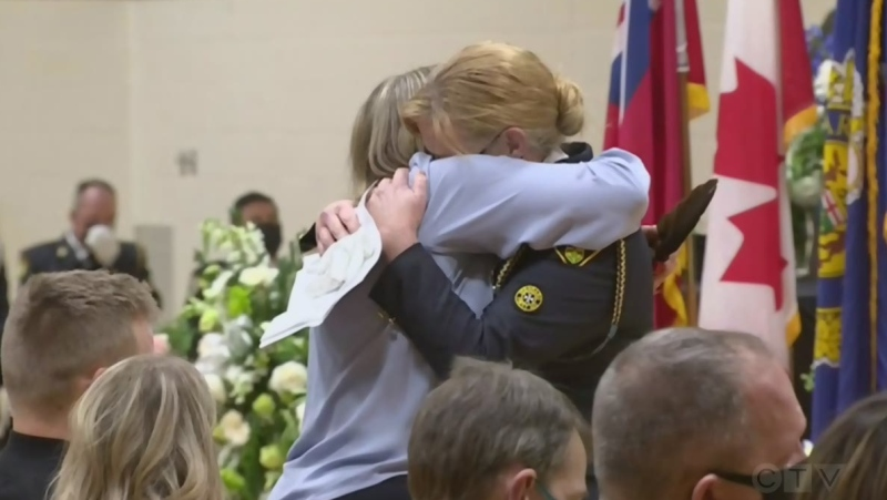 Marc's widow Lianne hugs one of his colleagues