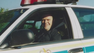Photo of a young Marc Hovingh in a police car (Supplied)