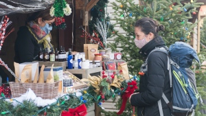 A woman wears a face mask as she shops at a Christmas market in Montreal, Saturday, November 28, 2020, as the COVID-19 pandemic continues in Canada and around the world. THE CANADIAN PRESS/Graham Hughes