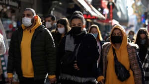 People wearing masks to help protect against the spread of coronavirus, walk in Ankara, Turkey, Friday, Nov. 27, 2020. (AP Photo/Burhan Ozbilici)