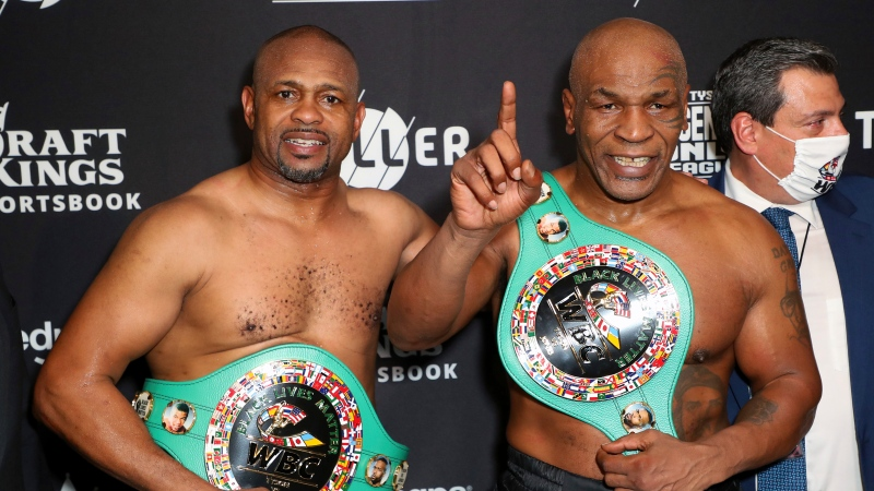 In a photo provided by Triller, Roy Jones Jr., left, and Mike Tyson pose for photos after their exhibition boxing bout Saturday, Nov. 28, 2020, in Los Angeles. The bout was unofficially ruled a draw by the WBC judges at ringside. (Joe Scarnici/Triller via AP)