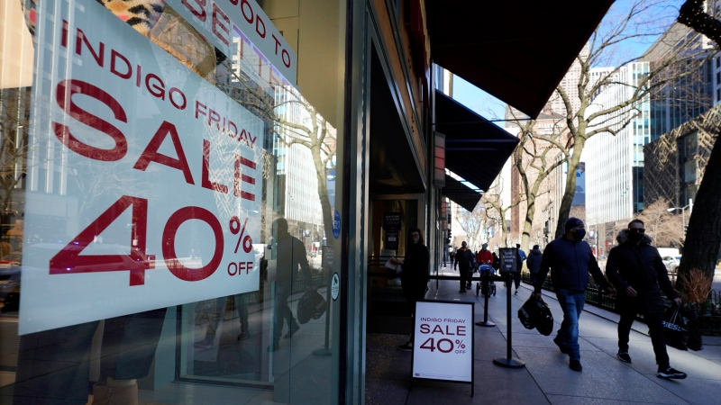 Shoppers pass an Indigo Friday 40% Off sign Saturday, Nov. 28, 2020, on Chicago's famed Magnificent Mile shopping district. (AP Photo/Charles Rex Arbogast)