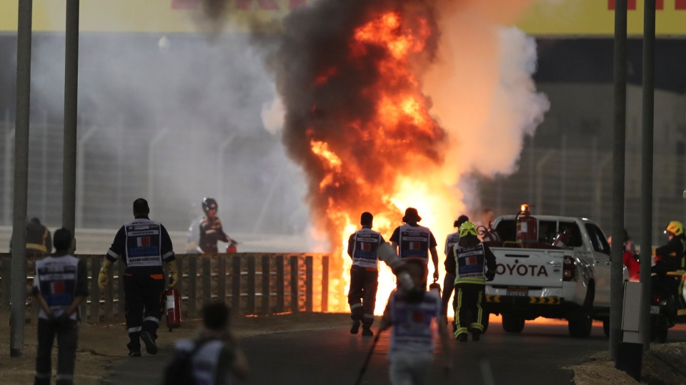 Marshals run to extinguish Haas driver Romain Grosjean's car after an accident during the Formula One Bahrain Grand Prix in Sakhir, Bahrain, Sunday, Nov. 29, 2020. (AP Photo/Kamran Jebreili, Pool)