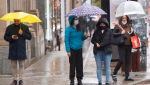 Pedestrians make their way through the rain as the walk along St. Catherine street in Montreal, Tuesday, Oct. 13, 2020. THE CANADIAN PRESS/Ryan Remiorz