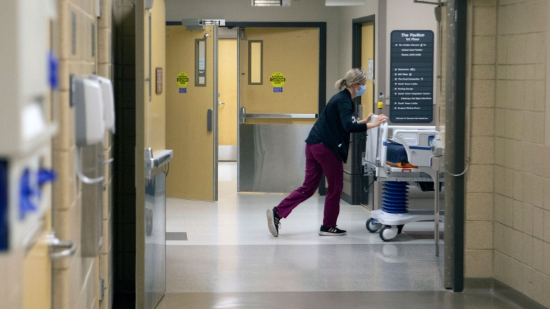 A nurse at Stormont Vail Health System pushes a hospital bed through hallways Wednesday, Nov. 18, 2020 in Topeka, Kan. Conditions inside the nation's hospitals are deteriorating by the day as the coronavirus rages through the country at an unrelenting pace. Stormont Vail Health in Topeka, Kansas, devoted an entire hospital floor to COVID-19 patients as their numbers swelled, hitting 90 on Wednesday. (Evert Nelson/The Topeka Capital-Journal via AP)