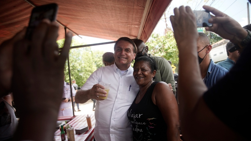Brazil's President Jair Bolsonaro, left, poses for a photo with a supporter after voting during run-off municipal elections in Rio de Janeiro, Brazil, Sunday, Nov. 29, 2020. (AP Photo/Silvia Izquierdo)