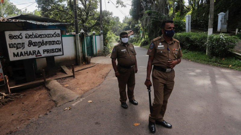 Sri Lankan police officers stand guard at the entrance to the Mahara prison complex following an overnight unrest in Mahara, outskirts of Colombo, Sri Lanka, Monday, Nov. 30, 2020. (AP Photo/Eranga Jayawardena)