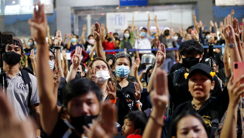 Protesters flash three-finger protest gestures as they gather to march in Bangkok, Thailand, Saturday, Nov. 28, 2020. (AP Photo/Sakchai Lalit)