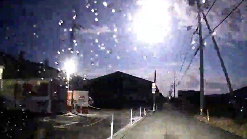 This image made from a drive recorder shows a brightly burning meteor, centre top, over a road in Tokushima prefecture, southwestern Japan, Sunday, Nov. 29, 2020. (Kamio via AP)