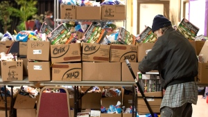 A recipient stacks his provisions in a cart at the Grant African Methodist Episcopal Church's Food Bank in Toronto on Friday March 20, 2020. (THE CANADIAN PRESS/Chris Young)
