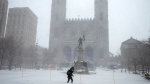 A pedestrian walks past Notre Dame Basilica during a snowstorm, Friday, February 7, 2020 in Montreal. THE CANADIAN PRESS/Ryan Remiorz