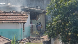 A Sri Lankan inmate of the Mahara prison carries a fellow inmate out from a damaged building, on Nov. 30, 2020. (Eranga Jayawardena / AP)