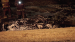 Calgary Fire Department members examine the charred wreckage following a Sunday night crash on 16 Ave. N.E. where a car left the road, flipped and caught fire